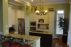 After: Lightened kitchen with new light fixtures and a granite countertop